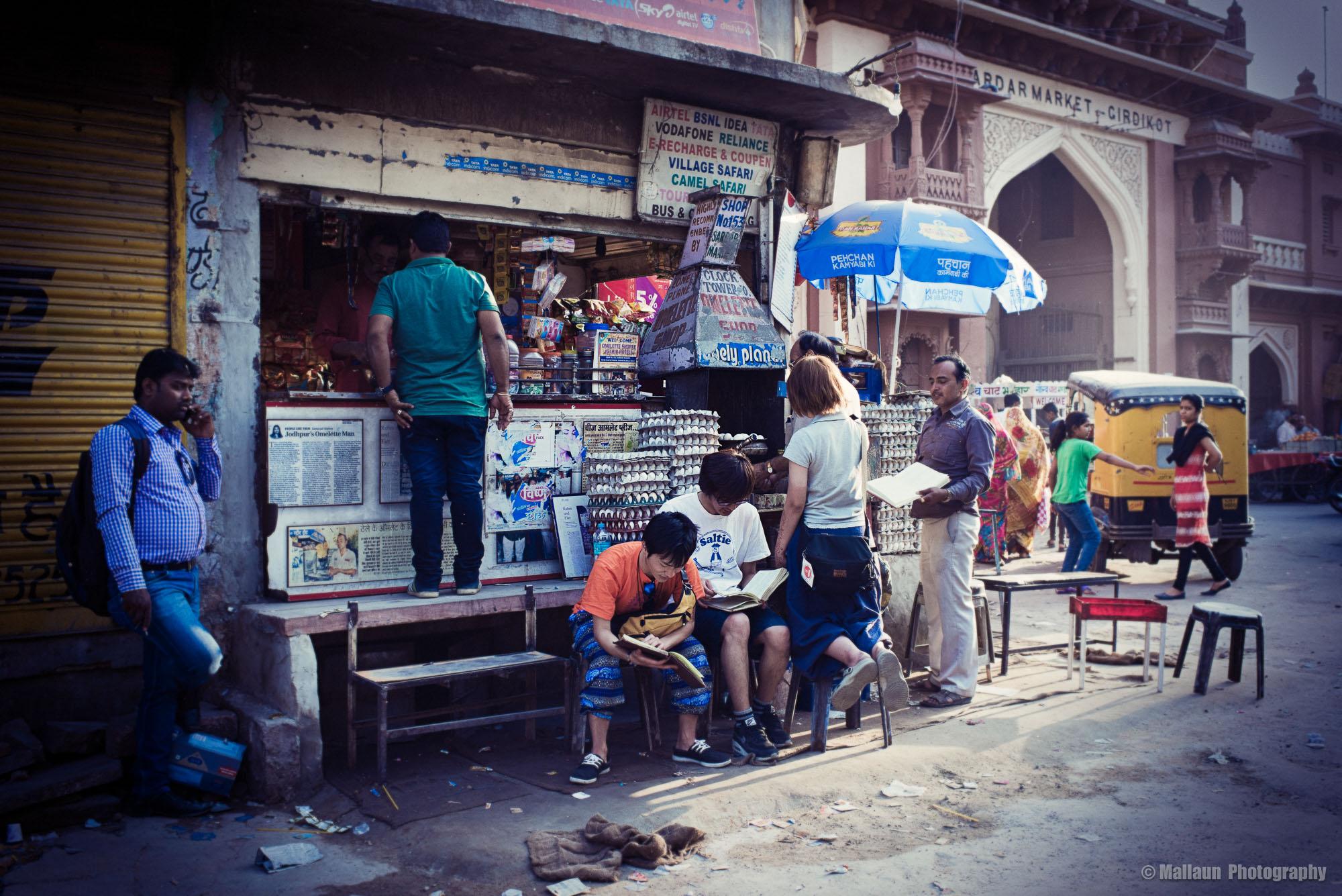 Der kleine Kiosk von Ramkishan steht direkt an der viel befahrenen Zufahrt zum berühmten Clock-Tower von Jodhpur. © Mallaun Photography