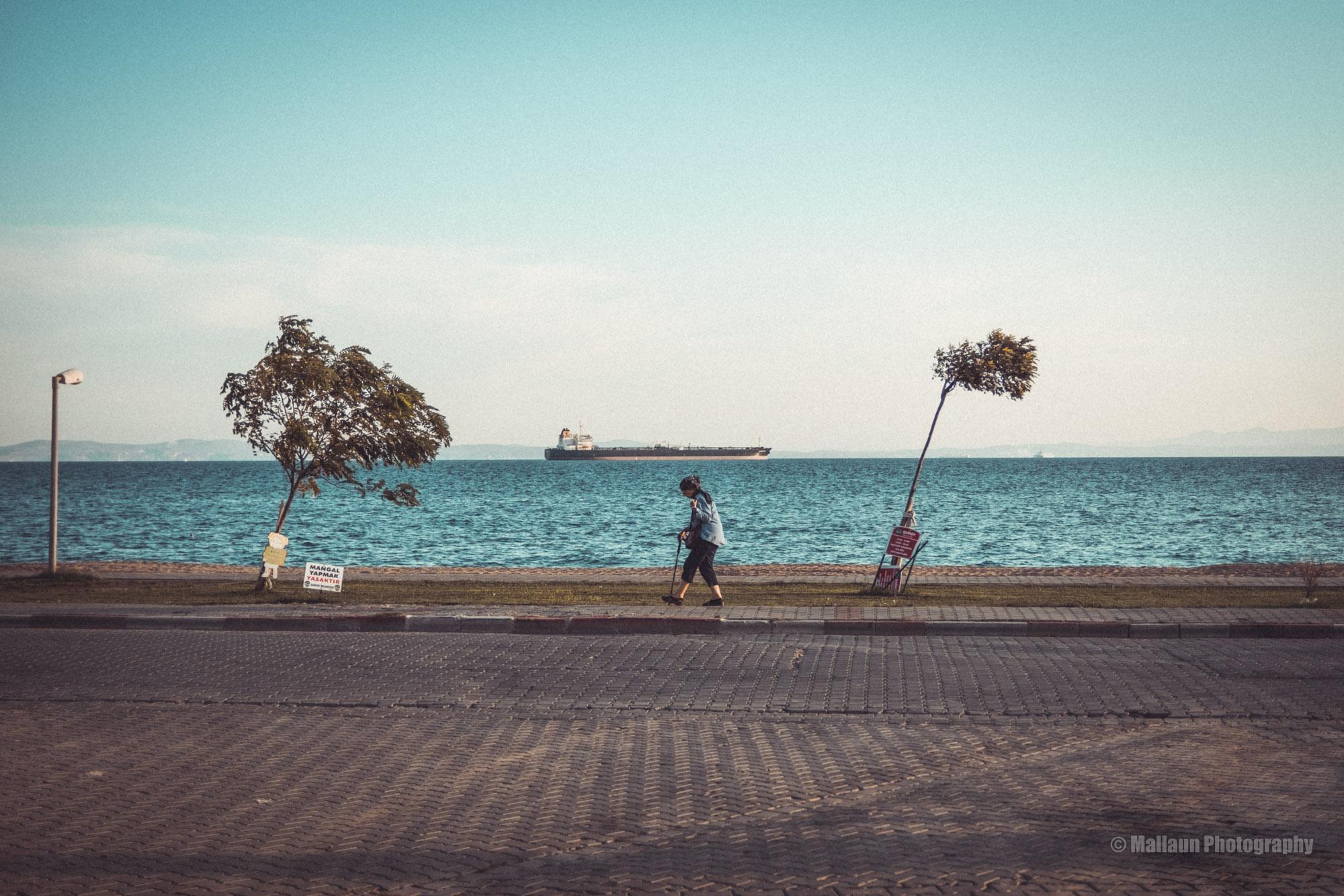 Schiefe Bäume und laufender Mensch mit Oeltanker im Hintergrund © Mallaun Photography