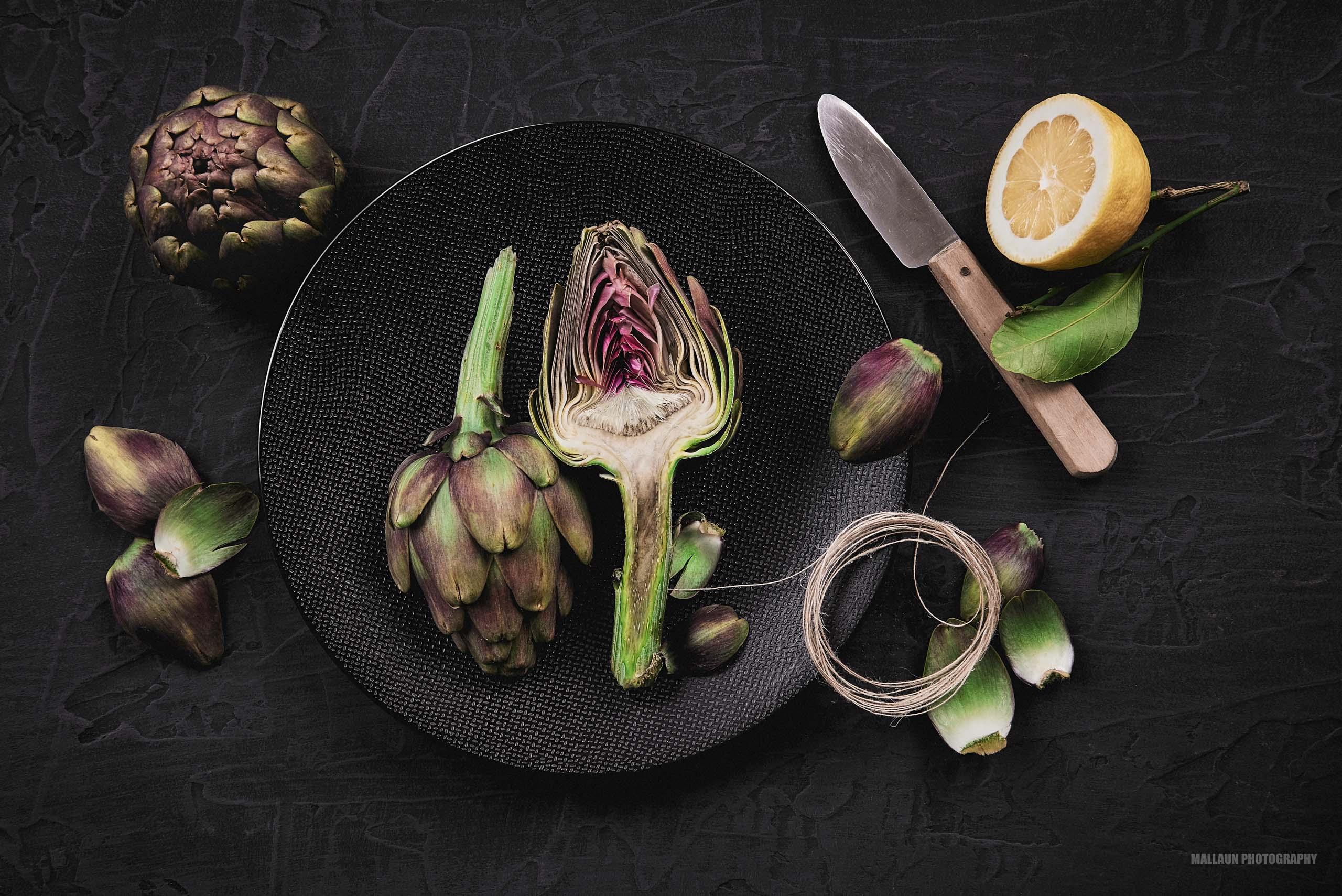 Schön angerichtete, aufgeschnittene Artischocke auf dunklem Teller und dunklem Foodboard.